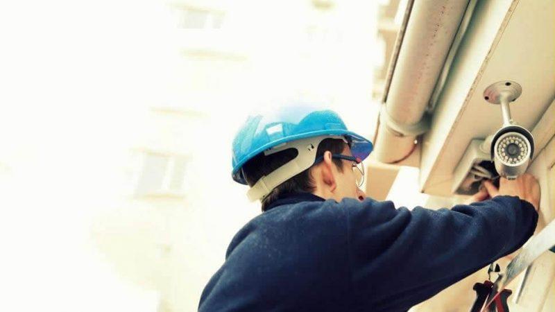 Hombre con casco azul colocando una cámara de seguridad en el techo de su casa