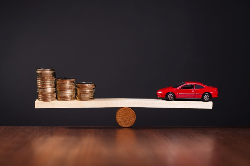 Balanza entre dinero y automóviles