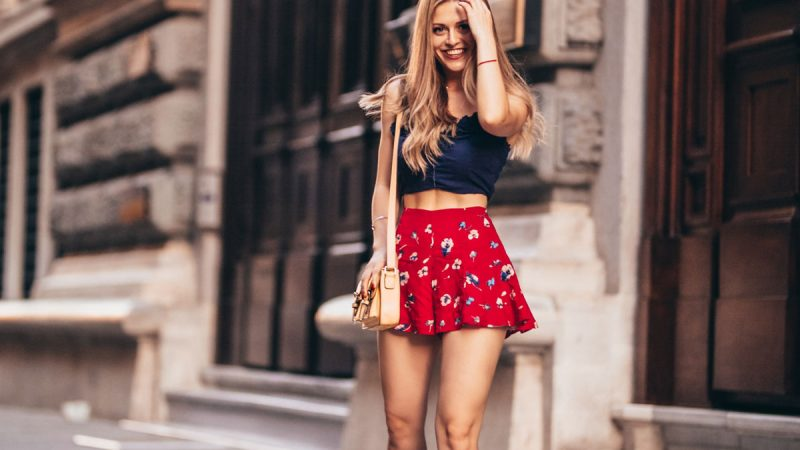 Mujer con mini falda roja posando en la calle
