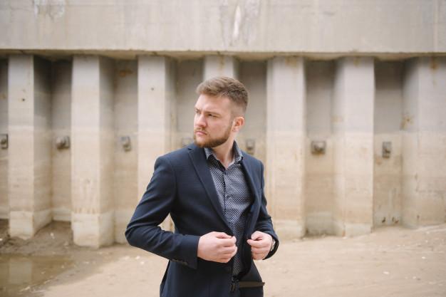 Hombre guero de traje en el exterior de un edificio